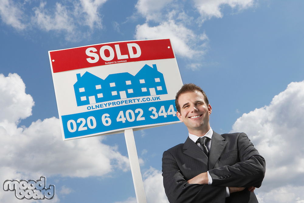 Real estate agent in front of sold sign against cloudy sky