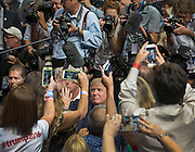GOP presidential hopeful Donald Trump is surrounded by fans and media as he leaves American Airlines Center in Dallas, Texas on September 14, 2015. Trump was holding a campaign rally as he runs for the GOP presidential nomination.