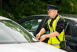 Edinburgh, Scotland, UK. 23 June, 2020. Parking attendant gives illegally parked car a ticket in Edinburgh. Starting from 22 June, Edinburgh City Council has begun to issue parking tickets following a suspension during the coronavirus pandemic.  Iain Masterton/Alamy Live News