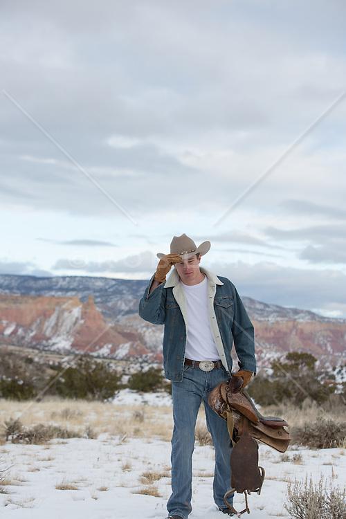 cowboy carrying a saddle through a snowy mountain pass