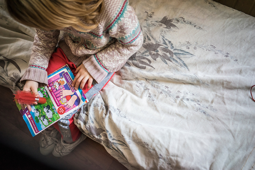 A young girl reads a magazine at Romashka, a summer camp where several hundred people live after being displaced by fighting in Eastern Ukraine on Friday, February 13, 2015 in Kharkiv, Ukraine.
