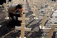 THE NETHERLANDS-THE HAGUE- Protest against the Death Penalty in the United States...Foto: Gerrit de Heus. Den Haag. 01/12/05. Amnesty International protesteert met het plaatsen van duizend kruizen voor de Amerikaanse ambassade tegen het behalen van de macabere mijlpaal van 1000 executies. Bart Stapert, voorzitter van Amnesty International en voormalig advocaat van terdoodveroordeelden legt bloemen bij gedenkkruizen van mensen die hij zelf verdedigd heeft.