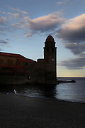 Plage du Boramar and Eglise Notre Dame des Anges at dusk, Collioure, France. The bell tower was converted from a medieval lighthouse and the Mediterranean Gothic style nave was built in 1684. The dome was added to the bell tower in 1810. Picture by Manuel Cohen.