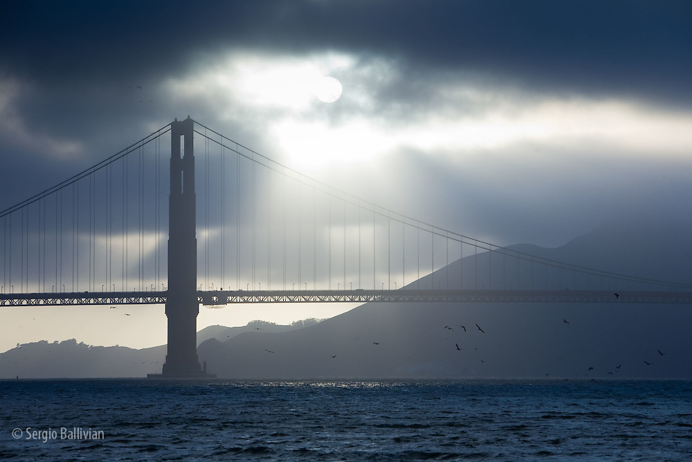 Sunset behind the Golden Gate Bridge under cloudy skies as ships head out to sea and people play on the beach.
