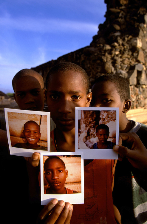 Children photographed with their Polaroids next to the Cidade Velha Basilica's ruins.