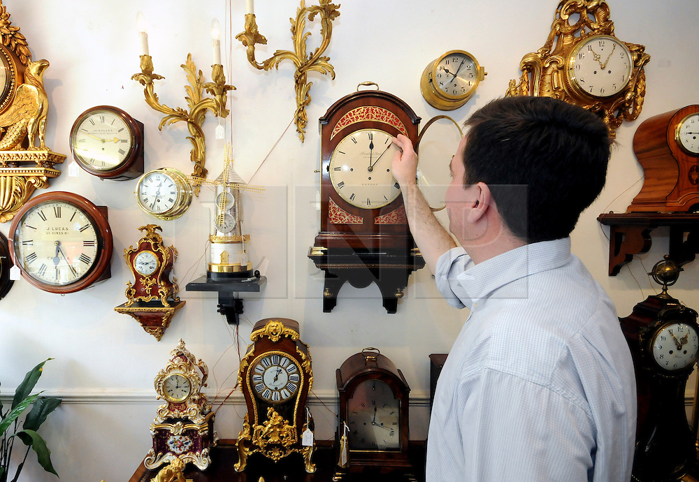 © under license to London News Pictures. 25/10/2010. FILE PICTURE. GMT returns on Saturday as the clocks are turned back for the onset of winter. Mark Coxhead, 40,  begins the long task of changing the hundreds of clocks in his clock shop. Mark and his father opened Gutlin Clocks and Antiques in 1994 on Kings Road in Chelsea and have sold clocks to the Royal Family and are responsible for clocks at the Home Office, Scotland office and all of London's Law Courts