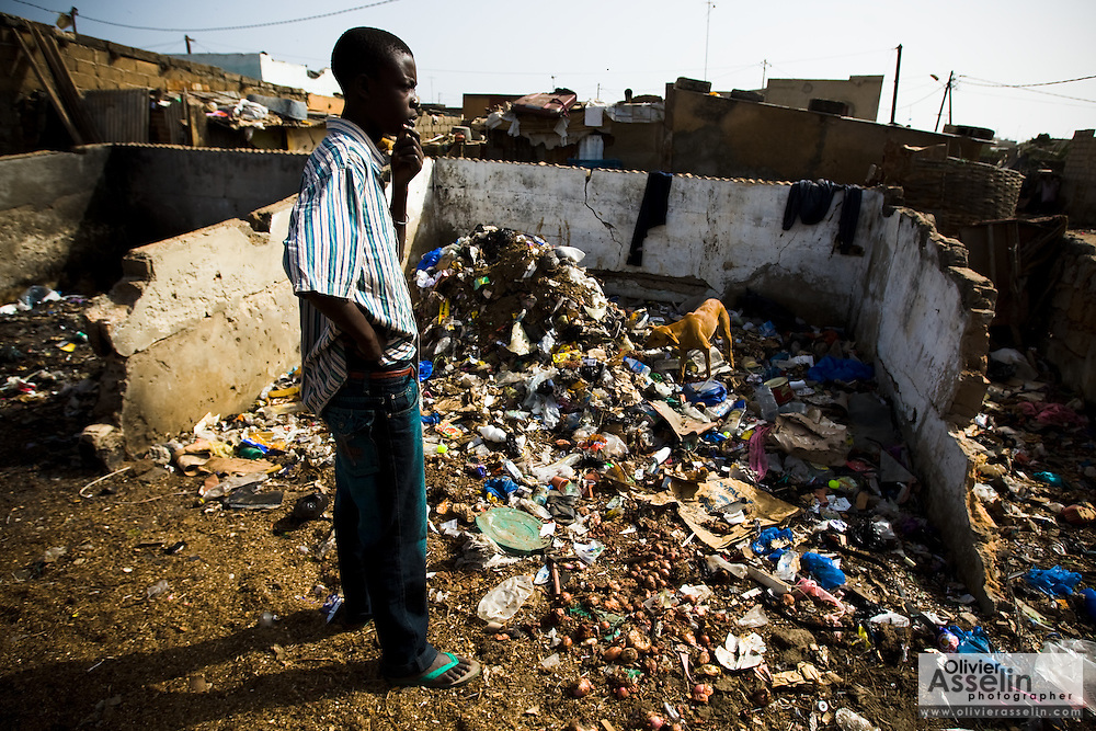 A resident stands among the ruins of a home partially buried in garbage  in the Medina Gounass neighborhood of Guediawaye, Senegal on Friday May 1, 2009. (Olivier Asselin for the New York Times)