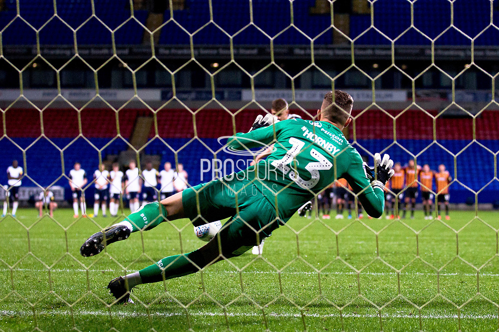 Bolton Wanderers defender Adam Senior has his penalty kick saved from Bradford City goalkeeper Sam Hornby during the EFL Trophy match between Bolton Wanderers and Bradford City at the University of  Bolton Stadium, Bolton, England on 3 September 2019.