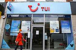 © Licensed to London News Pictures. 13/05/2020. London, UK. A woman wearing a face covering walks past a Tui branch in north London. Tui Group is to cut 8,000 jobs worldwide after losing £747m in 2020 due to COVID-19. Photo credit: Dinendra Haria/LNP