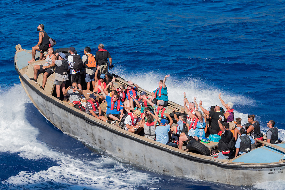 Pitcairn Island, Pacific Ocean-- March 27, 2018.  Natives of Pitcairn Island wave to as they begin the sail  home after visiting a nearby cruise ship. Editorial Use Only.