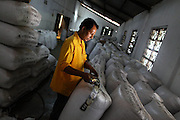 Worker in a tea factory preparing the bags for expedition (to Chittagong, for auction sales).