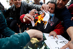 Protestors burn posters of Libyan leader Muammar Gaddafi during a protest outside the Libyan Embassy in Attard, outside Valletta, February 22, 2011. The protest was organised by the Libyan community living in Malta against the Libyan government's crackdown on demonstrators in Libya..Photo by Darrin Zammit Lupi