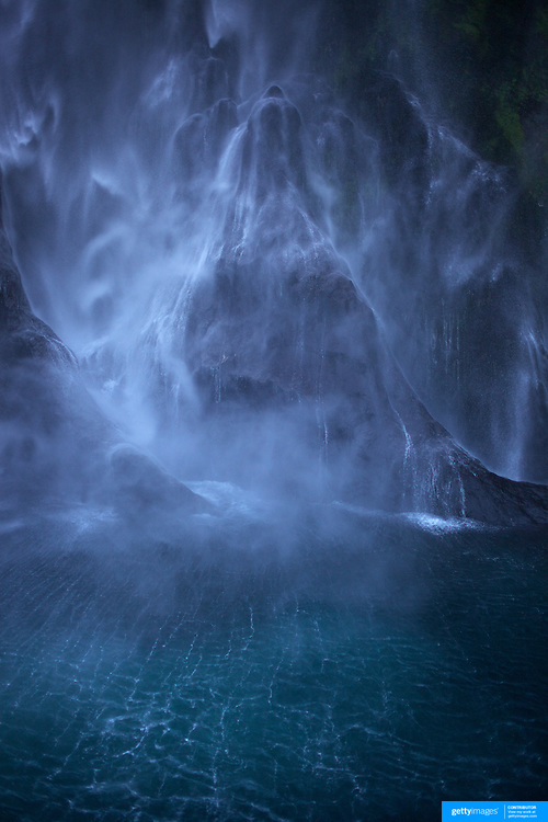 The spectacular Stirling Falls on Milford Sound..Milford Sound (Piopiotahi in Ma¯ori) is a fjord in the south west of New Zealand's South Island, within Fiordland National Park and the Te Wahipounamu World Heritage site. It has been judged the world's top travel destination and is acclaimed as New Zealand's most famous tourist destination..Milford Sound runs 15 kilometres inland from the Tasman Sea at Dale Point - the mouth of the fiord - and is surrounded by sheer rock faces that rise 1,200metres (3,900ft) or more on either side. Among the peaks are The Elephant at 1,517metres (4,977ft), said to resemble an elephant's head and The Lion, 1,302metres (4,272ft), in the shape of a crouching lion. Lush rain forests cling precariously to these cliffs, while seals, penguins, and dolphins frequent the waters and whales can be seen sometimes..Milford Sound sports two permanent waterfalls all year round, Lady Bowen Falls and Stirling Falls. After heavy rain many hundreds of temporary waterfalls can be seen running down the steep sided rock faces. .The beauty of this landscape draws thousands of visitors each day, with between 550,000 and 1 million visitors in total per year. This makes the sound one of New Zealand's most-visited tourist spots, and also the most famous New Zealand tourist destination.  Milford Sound, New Zealand. 29th April 2011. Photo Tim Clayton