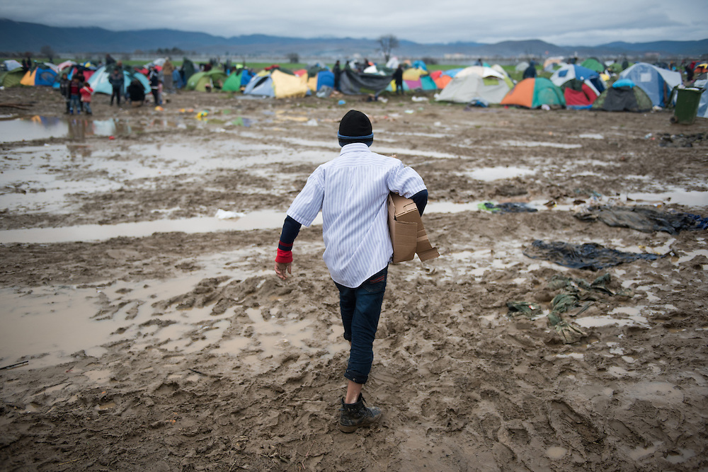 A tennager walks in a muddy field at the transit camp of Idomeni, Greece. <br /> <br /> Thousands of refugees are stranded in Idomeni unable to cross the border. The facilities are stretched to the limit and the conditions are appalling.