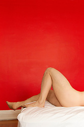 nude man's legs and butt on a bed against a red wall