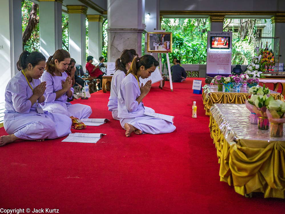 19 MAY 2013 - BANGKOK, THAILAND:  Women whose family members were killed by Thai soldiers in 2010 participate in a memorial service in Wat Pathum Wanaram in central Bangkok. More than 85 people, most of them civilians, were killed during the Thai army crackdown against the Red Shirt protesters in April and May 2010. The Red Shirts were protesting against the government of Abhisit Vejjajiva, a member of the opposition who became Prime Minister after Thai courts ruled the Red Shirt supported government was unconstitutional. The protests rocked Bangkok from March 2010 until May 19, 2010 when Thai troops swept through the protest areas arresting hundreds.   PHOTO BY JACK KURTZ