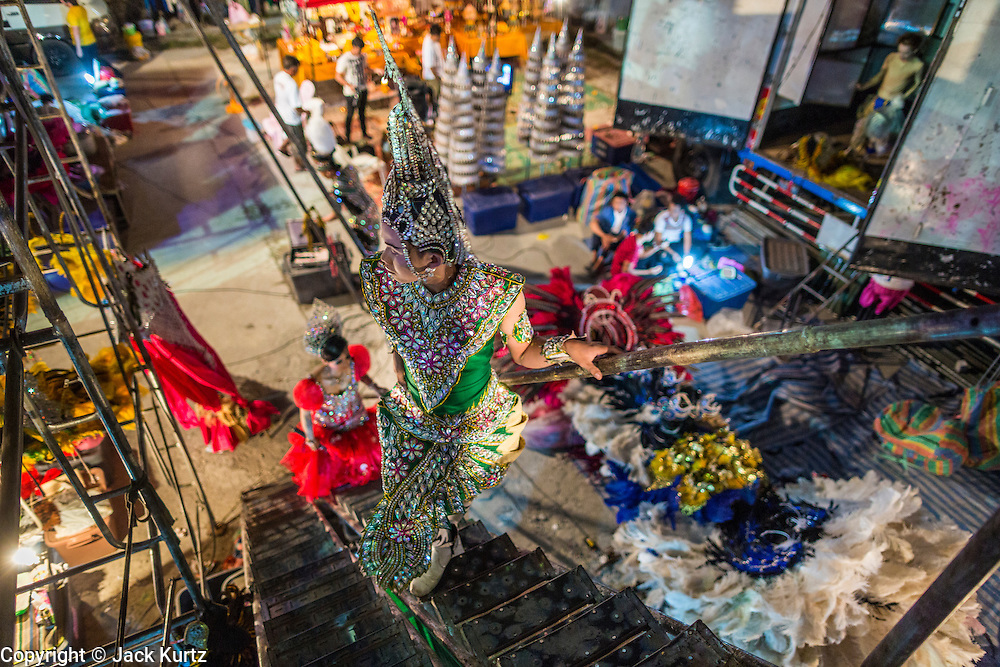 19 JANUARY 2014 - BANGKOK, THAILAND:  Performers in a mor lam show backstage in Khlong Tan Market in Bangkok. Mor Lam is a traditional Lao form of song in Laos and Isan (northeast Thailand). It is sometimes compared to American country music, song usually revolve around unrequited love, mor lam and the complexities of rural life. Mor Lam shows are an important part of festivals and fairs in rural Thailand. Mor lam has become very popular in Isan migrant communities in Bangkok. Once performed by bands and singers, live performances are now spectacles, involving several singers, a dance troupe and comedians. The dancers (or hang khreuang) in particular often wear fancy costumes, and singers go through several costume changes in the course of a performance. Prathom Bunteung Silp is one of the best known Mor Lam troupes in Thailand with more than 250 performers and a total crew of almost 300 people. The troupe has been performing for more 55 years. It forms every August and performs through June then breaks for the rainy season.              PHOTO BY JACK KURTZ