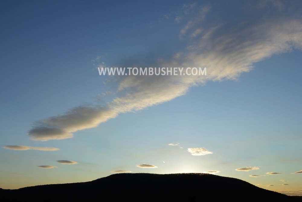 Chester, New York - The setting sun illuminates clouds over Goosepond Mountain State Park on April 7, 2012.