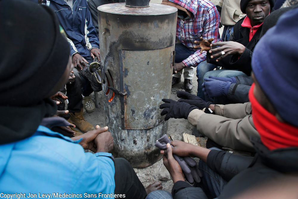 Refugees in the Calais refugee camp in northern France warm their hands with the heat from a wood-burning stove. <br />