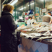 Fishmonger preparing the for a customer at Ribeira market.