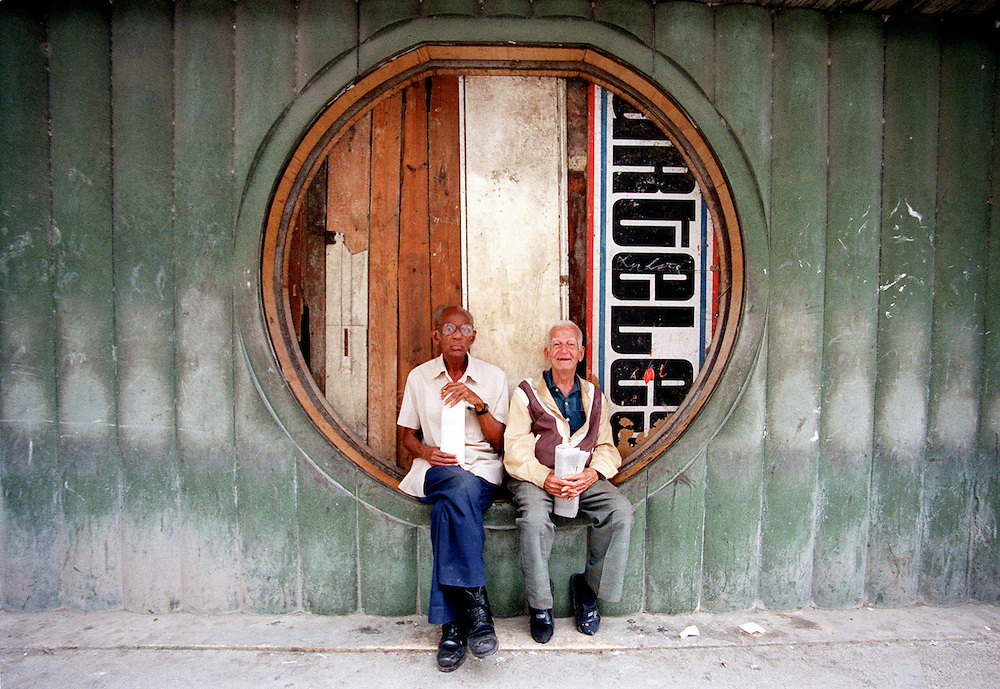 Elderly Cuban men sit in a boarded-up window of an old cinema in Havana, Cuba.