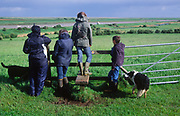AT5CH2 Country walk with people crossing a stile and looking over fields to Orford Ness, Suffolk, England