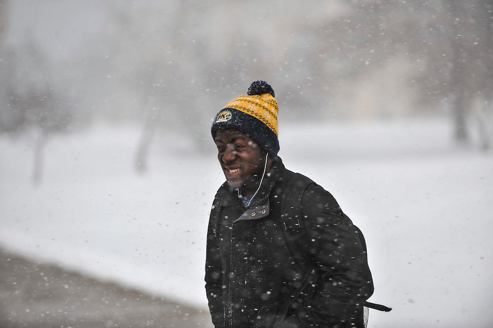 A student walks across Manchester Field during a winter snowstorm on the Kent Campus.