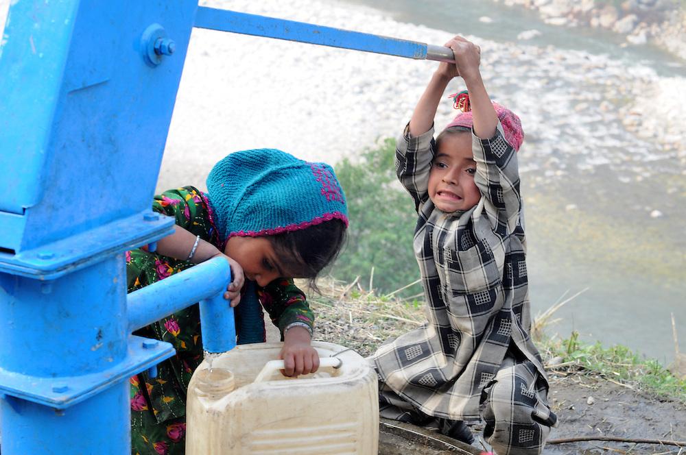 Rustem and Djennem Khatoon help fetch water from a roadside pump.