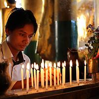 Lighting devotional candels at Shwedagon Pagoda