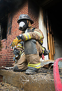 A firefighter kneels on the doorstep of a house that has been on fire.