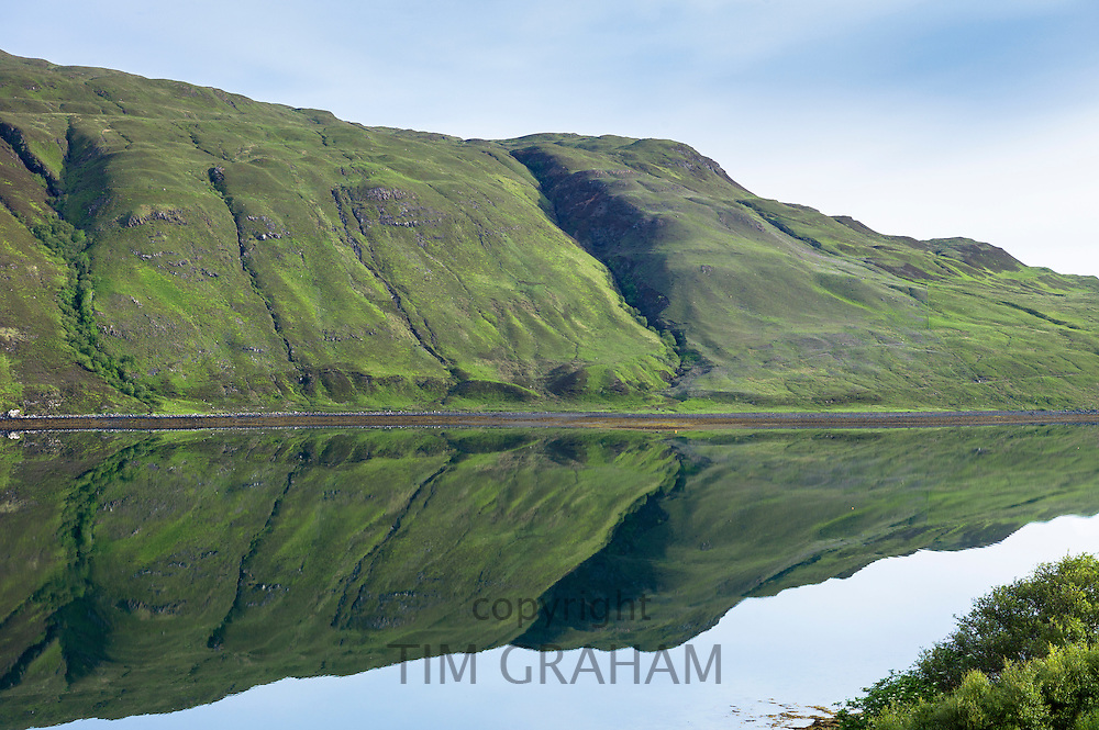 Mountain slopes reflected in the waters of a loch on Isle of Skye in the Highlands and Islands of Scotland