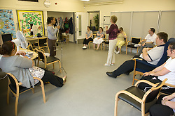 Day Service user with learning disabilities singing to a group of service users and one of the Care Assistants being encouraged by Day Service Officer,