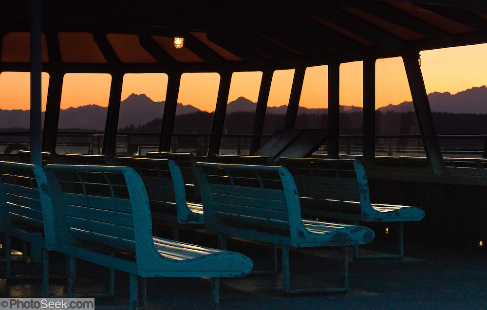 Sky over the Olympic Mountains glows orange at sunset seen from bench seats on the Edmonds to Kingston Ferry, Washington, USA.