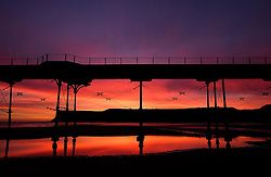 © Licensed to London News Pictures.25/10/15<br /> Saltburn, UK. <br /> <br /> Stunning colours light up the morning sky over the beach, pier and cliffs at Saltburn in Cleveland. <br /> <br /> Photo credit : Ian Forsyth/LNP
