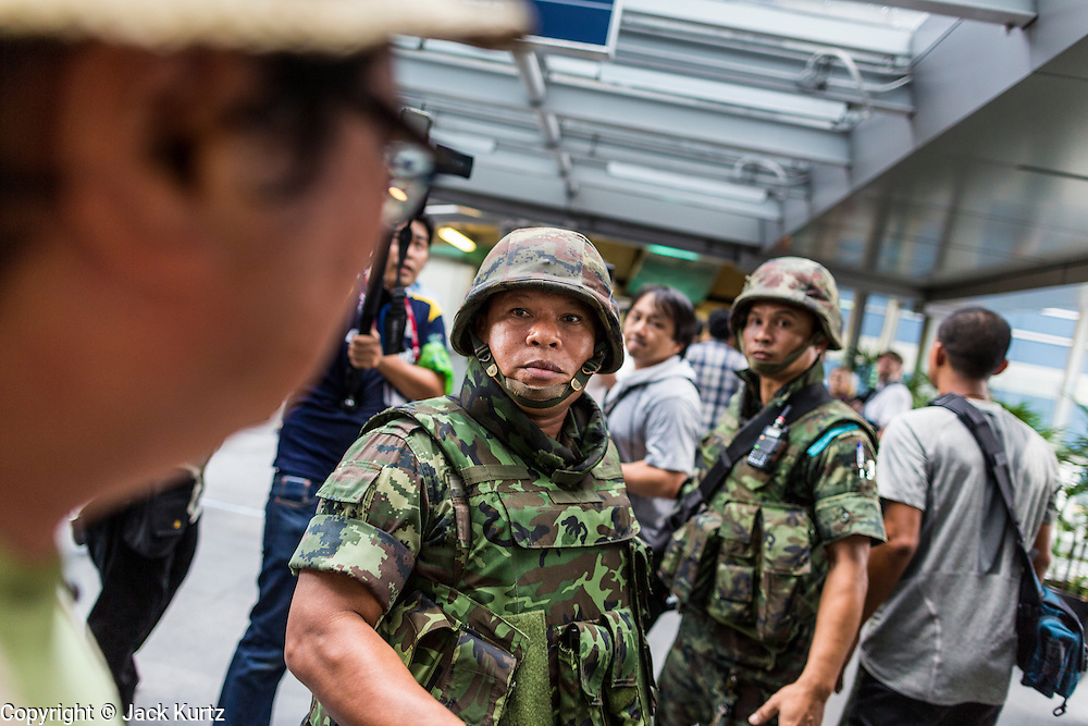 "01 JUNE 2014 - BANGKOK, THAILAND: Thai soldiers patrol the Asok BTS Skytrain station in Bangkok after a flash mob protested against the coup near the station. The Thai army seized power in a coup that unseated a democratically elected government on May 22. Since then there have been sporadic protests against the coup. The protests Sunday were the largest in several days and seemed to be spontaneous ""flash mobs"" that appeared at shopping centers in Bangkok and then broke up when soldiers arrived. Protest against the coup is illegal and the junta has threatened to arrest anyone who protests the coup. There was a massive security operation in Bangkok Sunday that shut down several shopping areas to prevent the protests but protestors went to malls that had no military presence.    PHOTO BY JACK KURTZ"