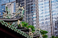 Ornate roof of Thean Hock Keng Temple contrasted against a modern skyscraper in Singapore.