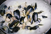 "NAPLES, ITALY - 12 SEPTEMBER 2018: Mussels and clams are cooked here at the Taverna del Buongustaio, a tavern in Naples, Italy, on September 12th 2018.<br /> <br /> Taverna del Buongustaio was founded in the 1930s by wine producer of the province of Caserta. Gaetano Aiese and his daughter Giusy have been managing the tavern since 1996. Customers of the Taverna are professors of the nearby University, students, merchants and employees of via Toledo, the commercial street right around the corner. Giusy and her father Gaetano decided to invest in the traditional Neapolitan cuisine. ""I learned cooking from my dad. And my dad learned cooking from his mother"", Giusy said."