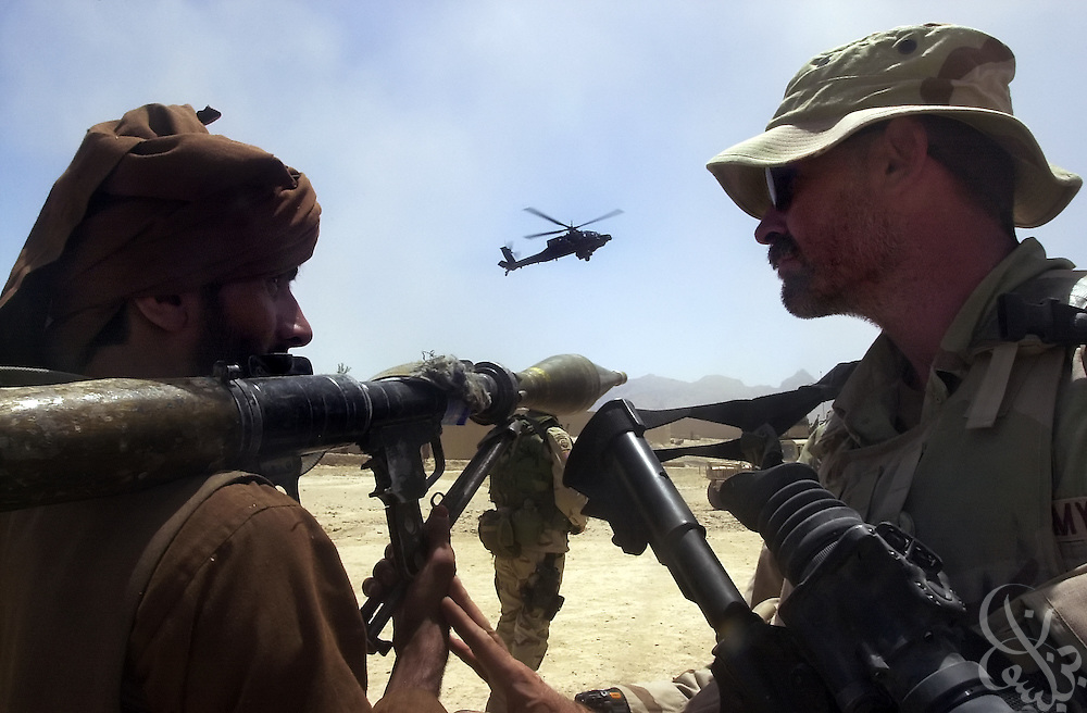 U.S. Army Special Forces soldier (R) gestures to a local Afghan gunman to lower his rocket propelled grenade (RPG) launcher as a U.S. Apache helicopter flies past during a July 7, 2002 visit by General Dan McNeill to the village of Deh Rawud in Southern Afghanistan. McNeill visited the village to speak with the regional governor and village elders about the possibility of stationing more U.S. troops in the region following an incident last week in which U.S. aircraft mistakenly targeted Afghan civilians celebrating in the village.