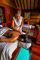 A woman getting a massage (with a glass window below her head on to view tropical fish in the lagoon outside) in the Kahaia spa suite at the Spa in the Four Seasons Resort Bora Bora, French Polynesia.