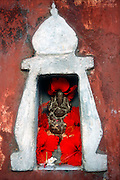 Sri Lanka..Small Ganesh in the wall of a Hindu Kovil in Trincomallee town. Hibiscus Hat.