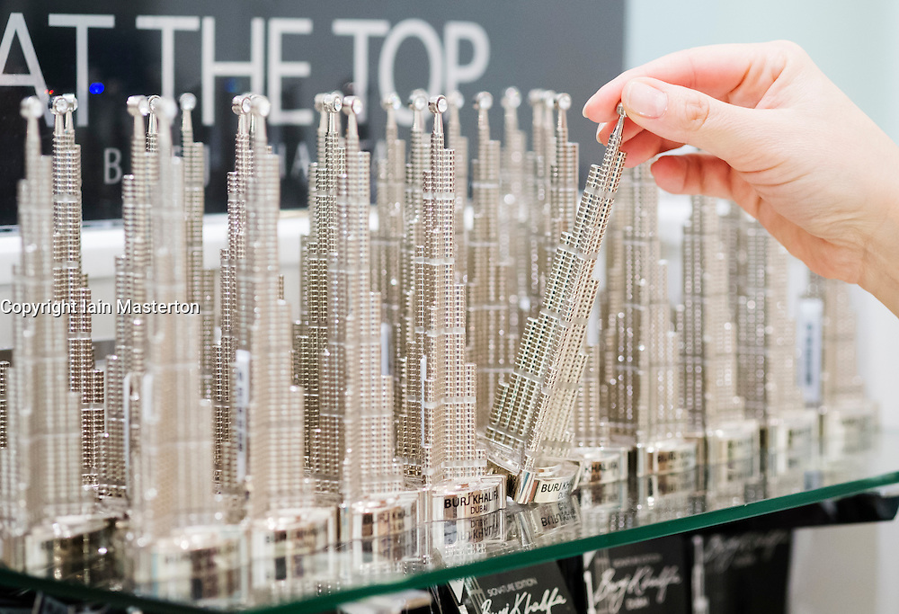 Tourist looking at souvenir models of the Burj Khalifa tower in At The Top observation deck gift shop in Dubai UAE