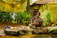 a woman cleaning the dishes in the backwaters near alleppey, india