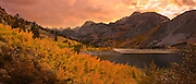 High resolution panoramic photograph of Fall color in the High Sierra up the Bishop Creek drainage at Lake Sabrina. The fields of aspen are turning gold and red and a first day of fall storm moved through creating a beautiful moody sunrise. Image stitched together from 8 frames, suitable for extremely large prints or display.