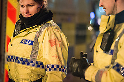 """© Licensed to London News Pictures . 20/12/2014 . Manchester , UK . Police with bloodstained uniforms . The officers had tended to a man with a head injury outside Deansgate Locks nightclub venue . The ambulance took over 40 minutes to arrive . """" Mad Friday """" revellers out in the rain and cold in Manchester . Mad Friday is typically the busiest day of the year for emergency services , taking place on the last Friday before Christmas when office Christmas parties and Christmas revellers enjoy a night out .  Photo credit : Joel Goodman/LNP"""