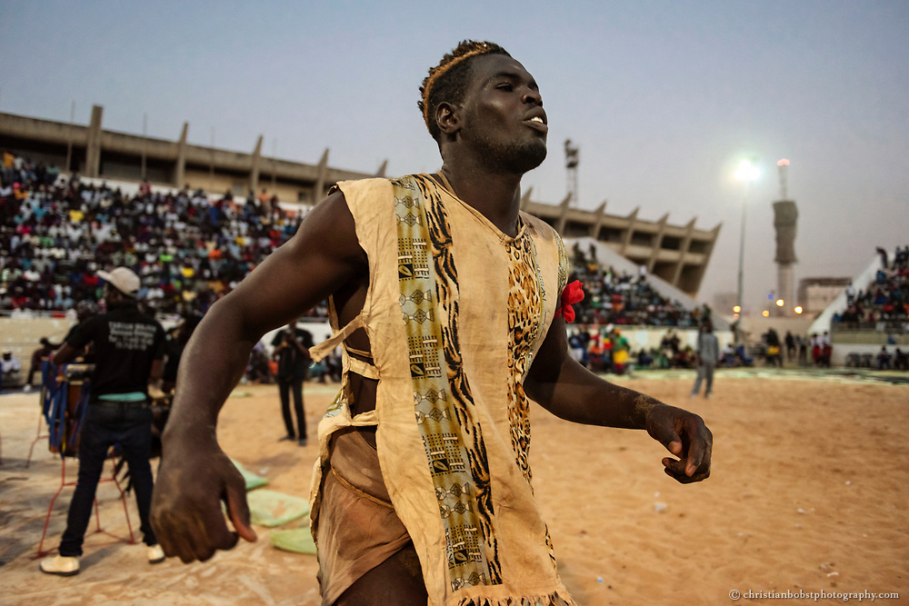 A wrestler warms up before a final fight in the Iba Mar Diop stadium, located in the Medina district in Dakar, March 29 2015. To prepare, he dances alone in a trance-like state to ear-deafening hypnotic drums and repetitive beats. The final fight is endowed with 700000 CFA (approx. 1200 US dollar).