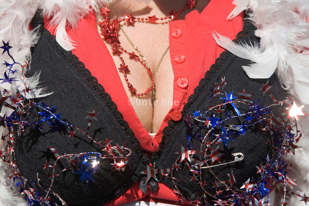 extreme close up of a woman's breast with a black bra on the outside of her clothing and American flag decoration