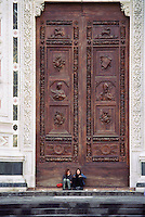 Two people sitting in front of giant doors Santa Croce Cathedral in Piazza Santa Croce Florence Italy