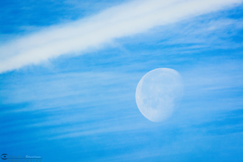 Daylight moon scene through morning vapor and contrails.