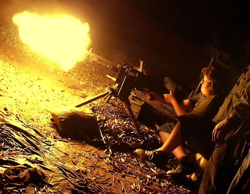 A boy fires his machine gun at the night shoot during the Knob Creek Machine Gun Shoot near West Point, Kentucky April 10, 2005. Thousands of machine gun and military hardware enthusiasts attended the event held each year over weekends in the spring and fall.