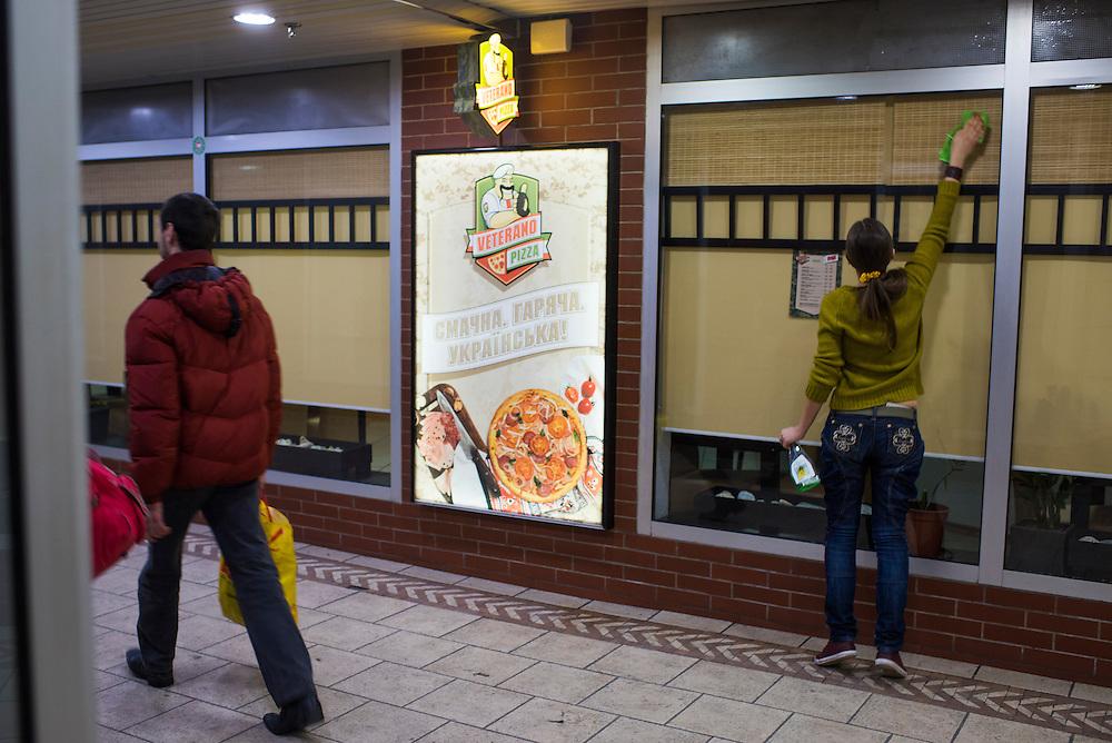 Veronica Ryzhenkowa, a non-veteran employee, cleans windows before opening at Veterano Pizza on January 23, 2016 in Kiev, Ukraine. (Pete Kiehart for The New York Times)